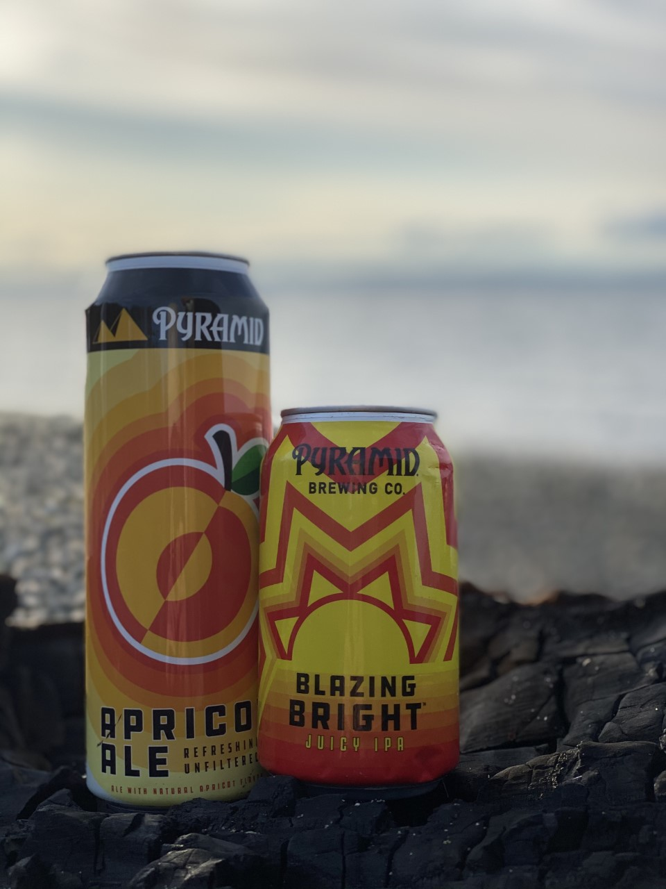 Two cans of Pyramid beer(Apricot Ale and Blazing Bright IPA) sit on a rock with a rocky shoreline in the background.