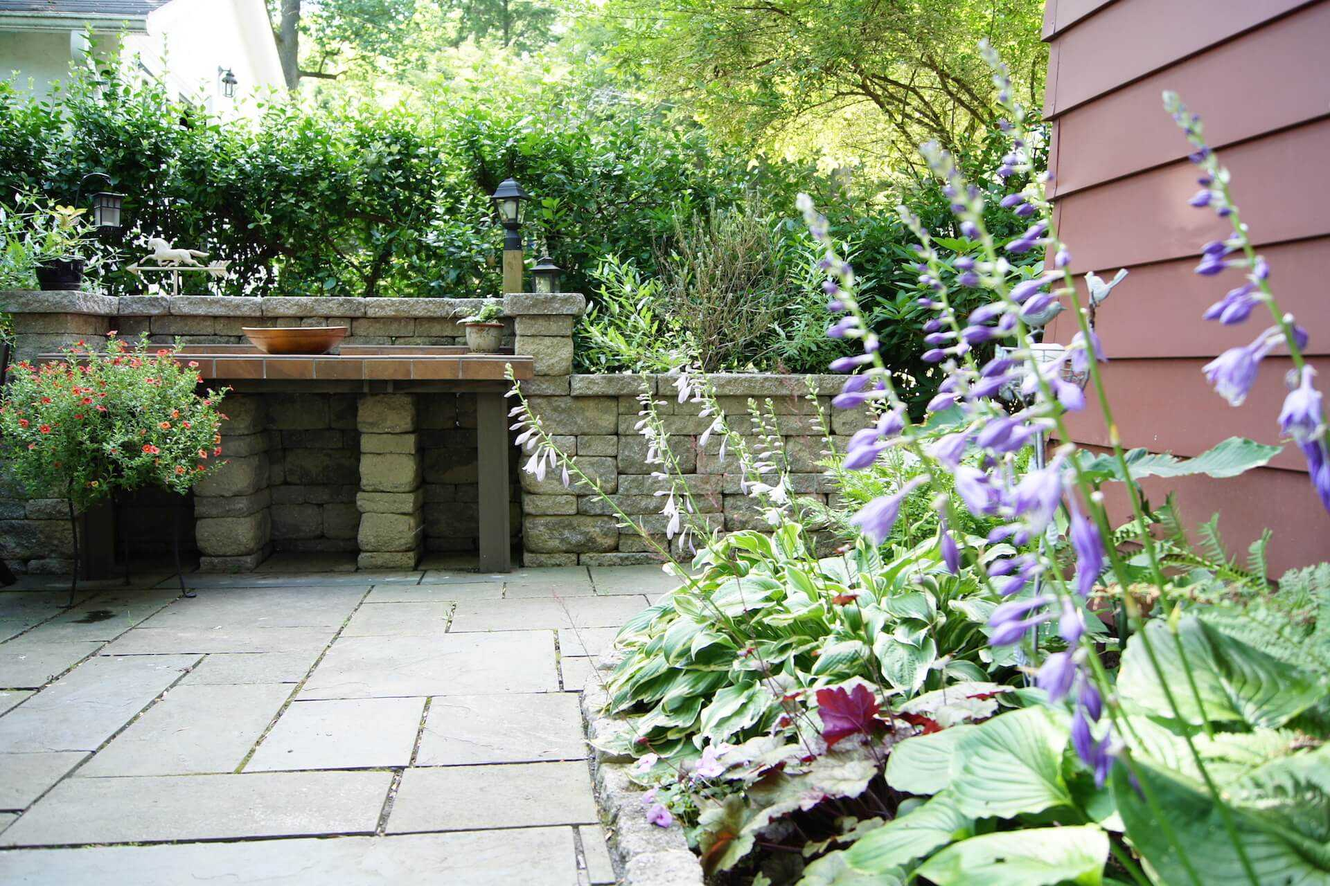 edge of flower bed facing stone table surface