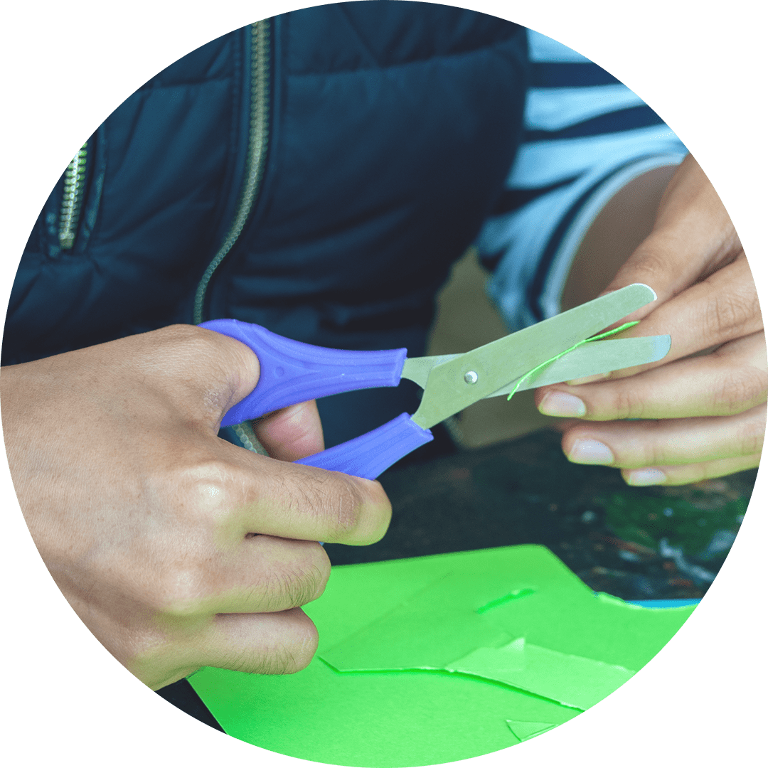 a close-up view of the hands of an online workshop participant cutting a piece of lime green cardstock with a small pair of purple scissors