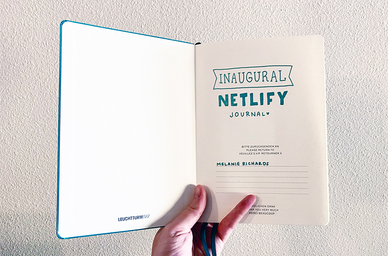 A teal journal opened to the first page, where I have written in teal pen 'Inaugural Netlify journal'