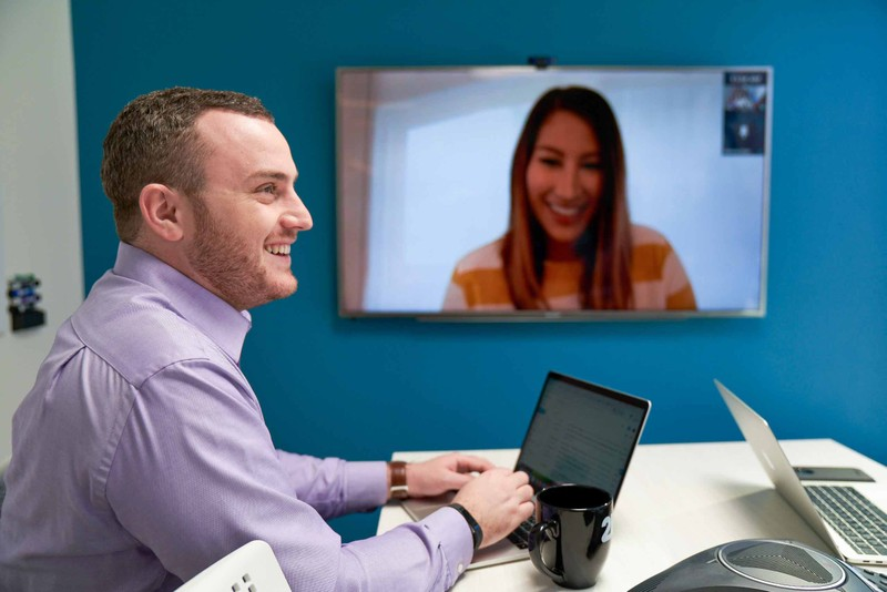 Smiling man typing on a laptop during a video conference