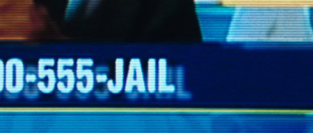 Showing the tail end of the phone number that characters within the film should call: 1-800-555-JAIL