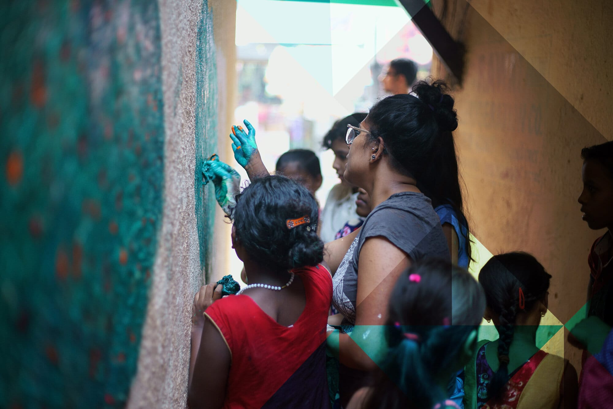 Children painting a mural on a wall