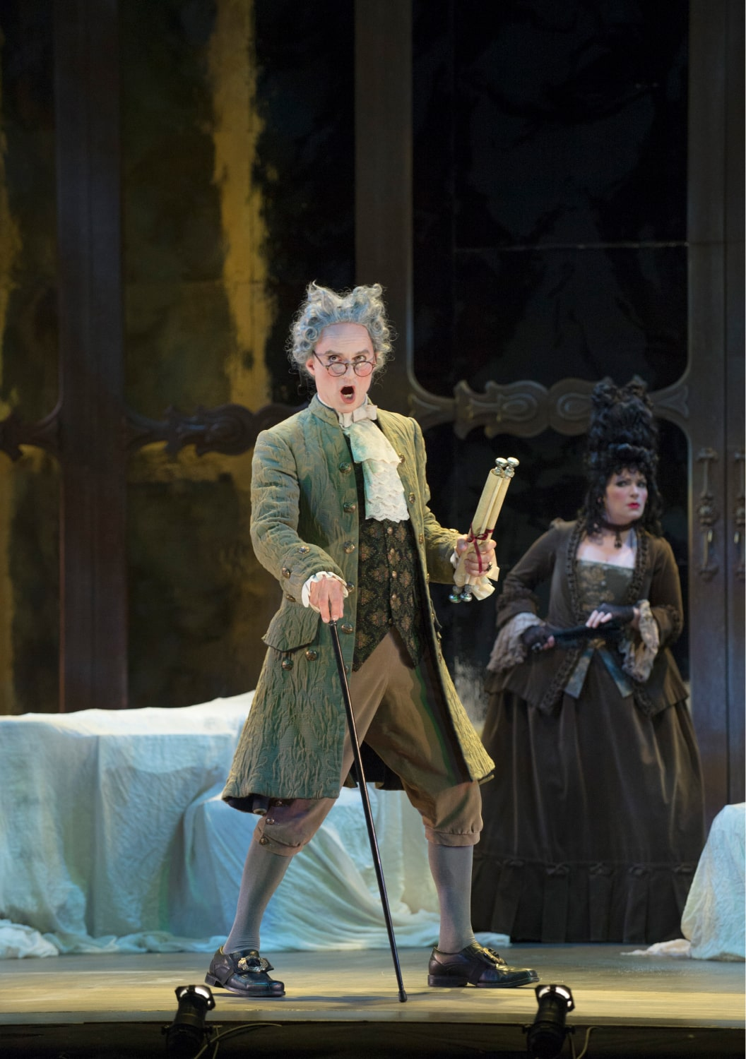 Green-frocked singer in powdered wig stands in footlights in front of throw-covered furniture watched by woman in background.