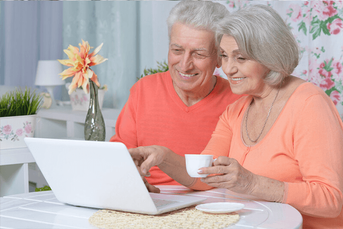 two aged adults looking at a computer and smiling