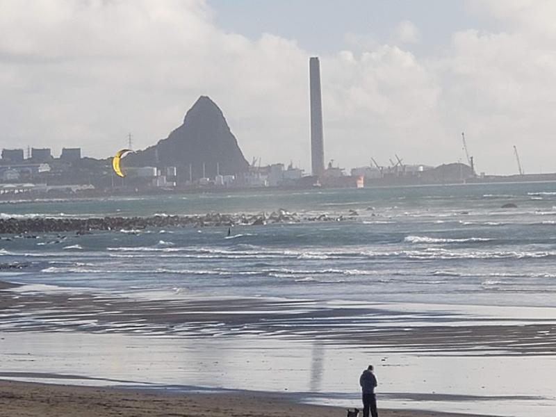 Looking toward the port of New Plymouth and watching Trevor kite surfing (yellow kite)