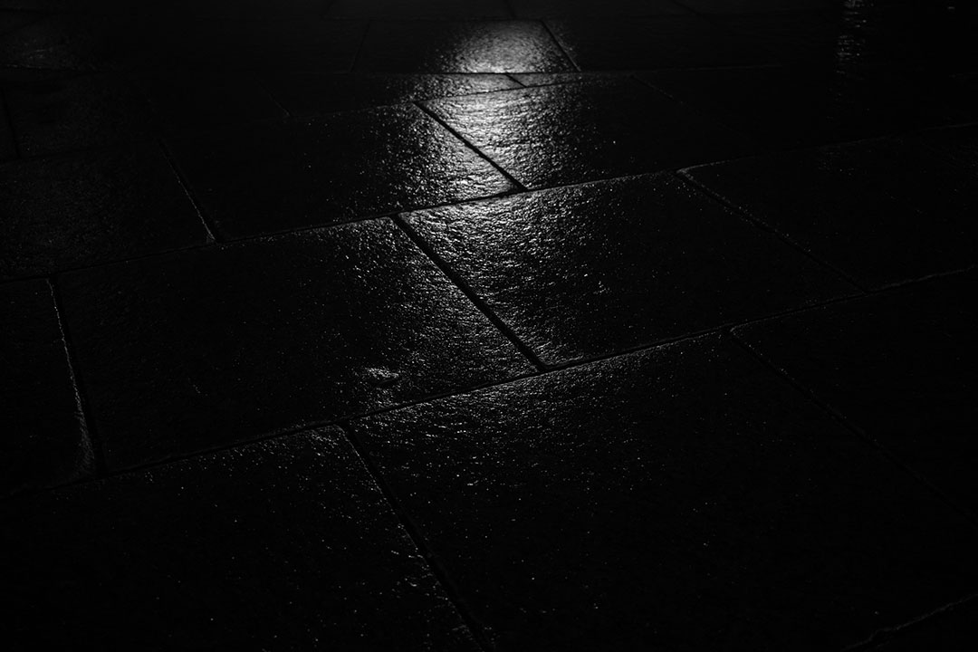Light reflecting on wet stone tiles in black and white at night.