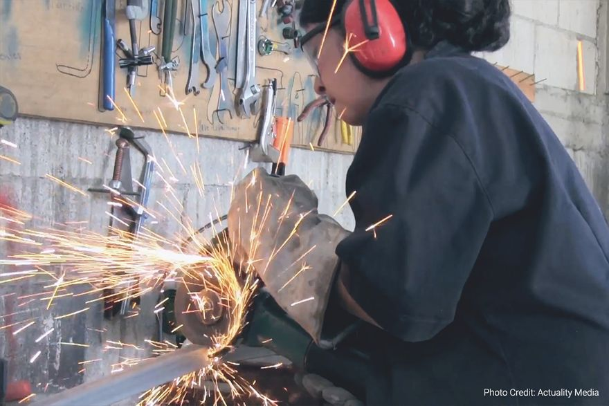 a woman wearing protective gear uses an angle grinder to cut a piece of metal (photo credit: actuality media)