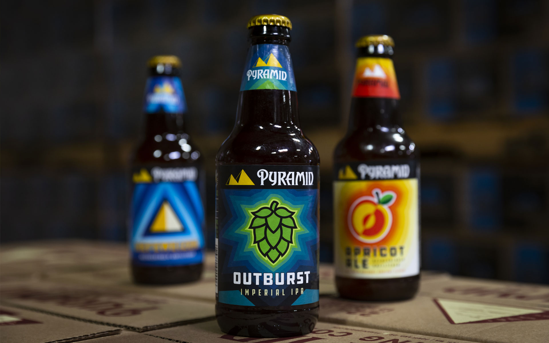 Closeup of an Outburst bottle with Apricot Ale and Hefeweizen in the background on Pyramid boxes
