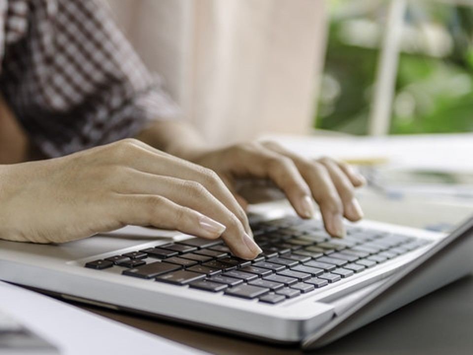 The hands of a man typing in a laptop