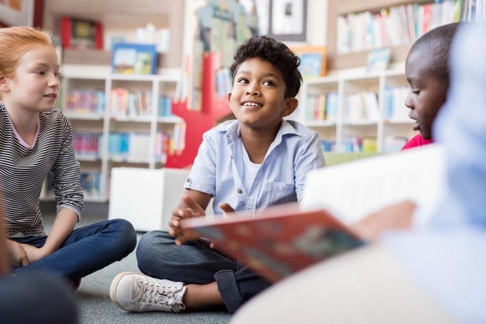 Teacher reads to elementary school children in library.