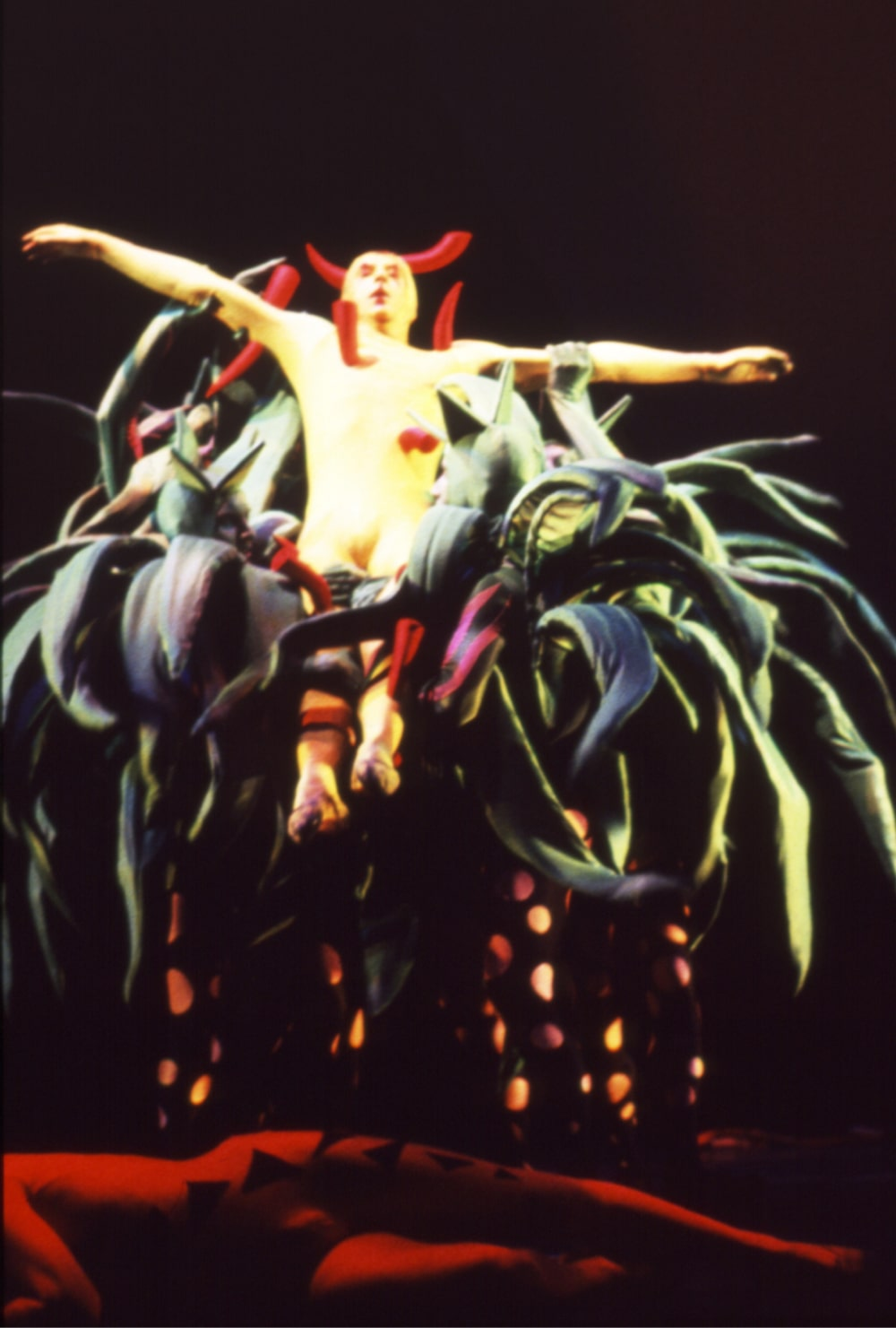 Dancer in yellow leotard pierced by large red thorns is held aloft by cactus people.