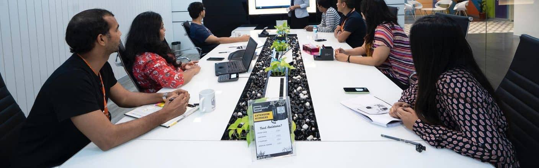 Trainerin mit Kursteilnehmern während einer MS-Office Firmenschulung