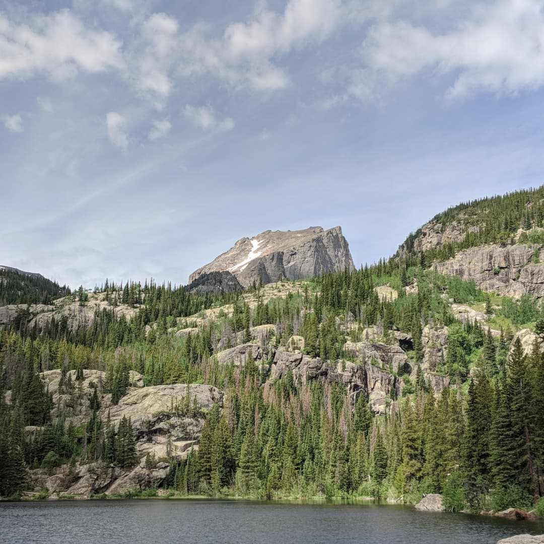 A sheer, angular peak rises above the valley walls surrounding a mountain lake.