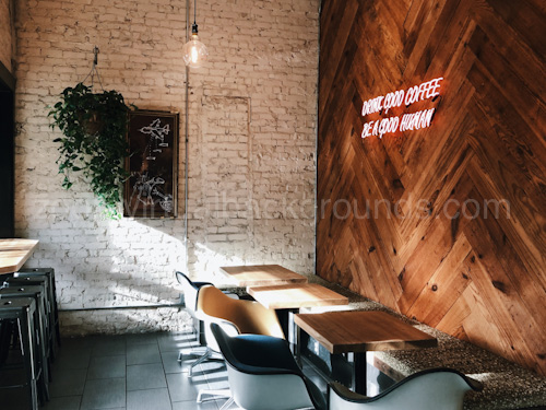 Cafe Virtual Background for Zoom with small wooden tables and neon sign on wall