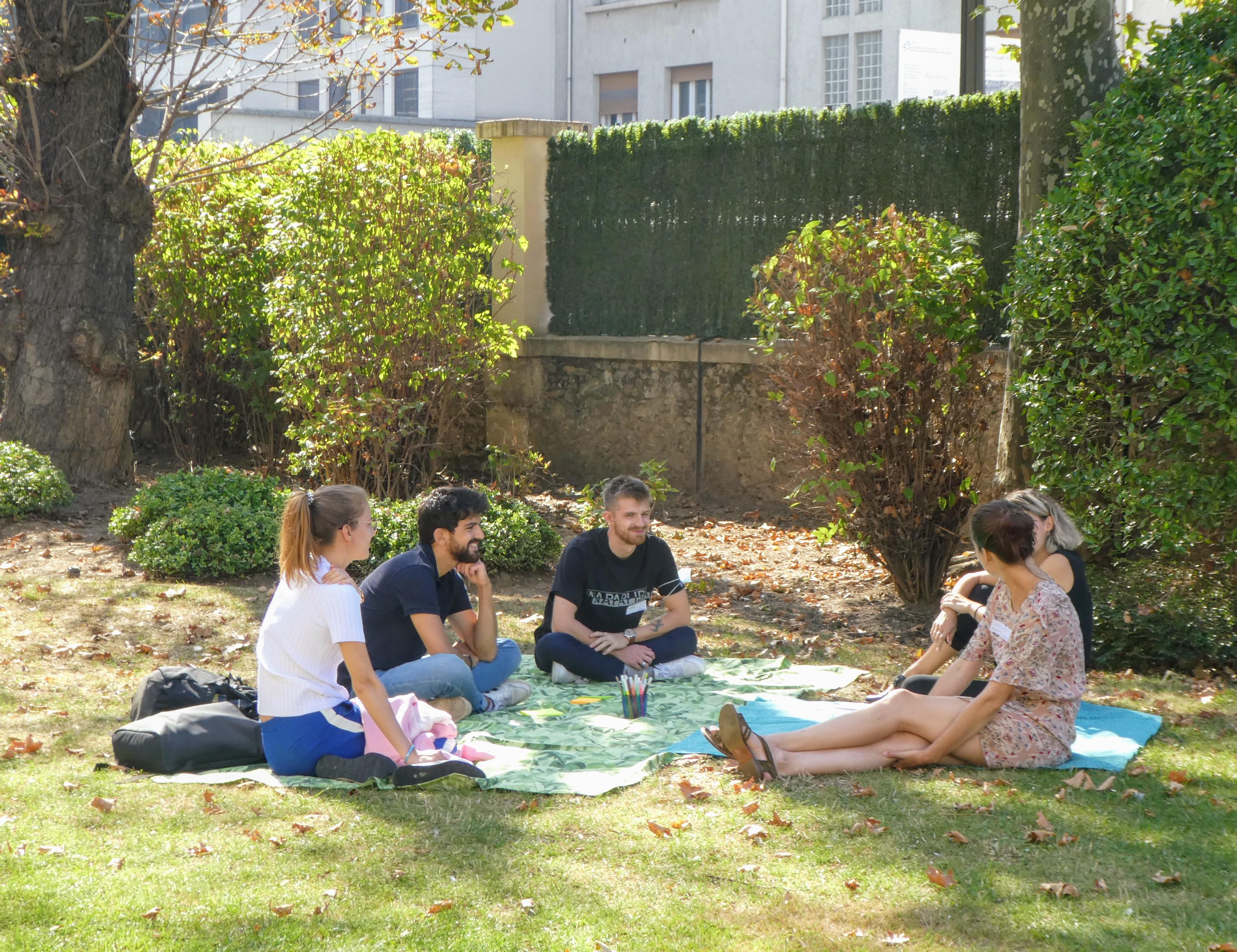 Cinq personnes discutent, assises dans l'herbe. Elles sont souriantes.