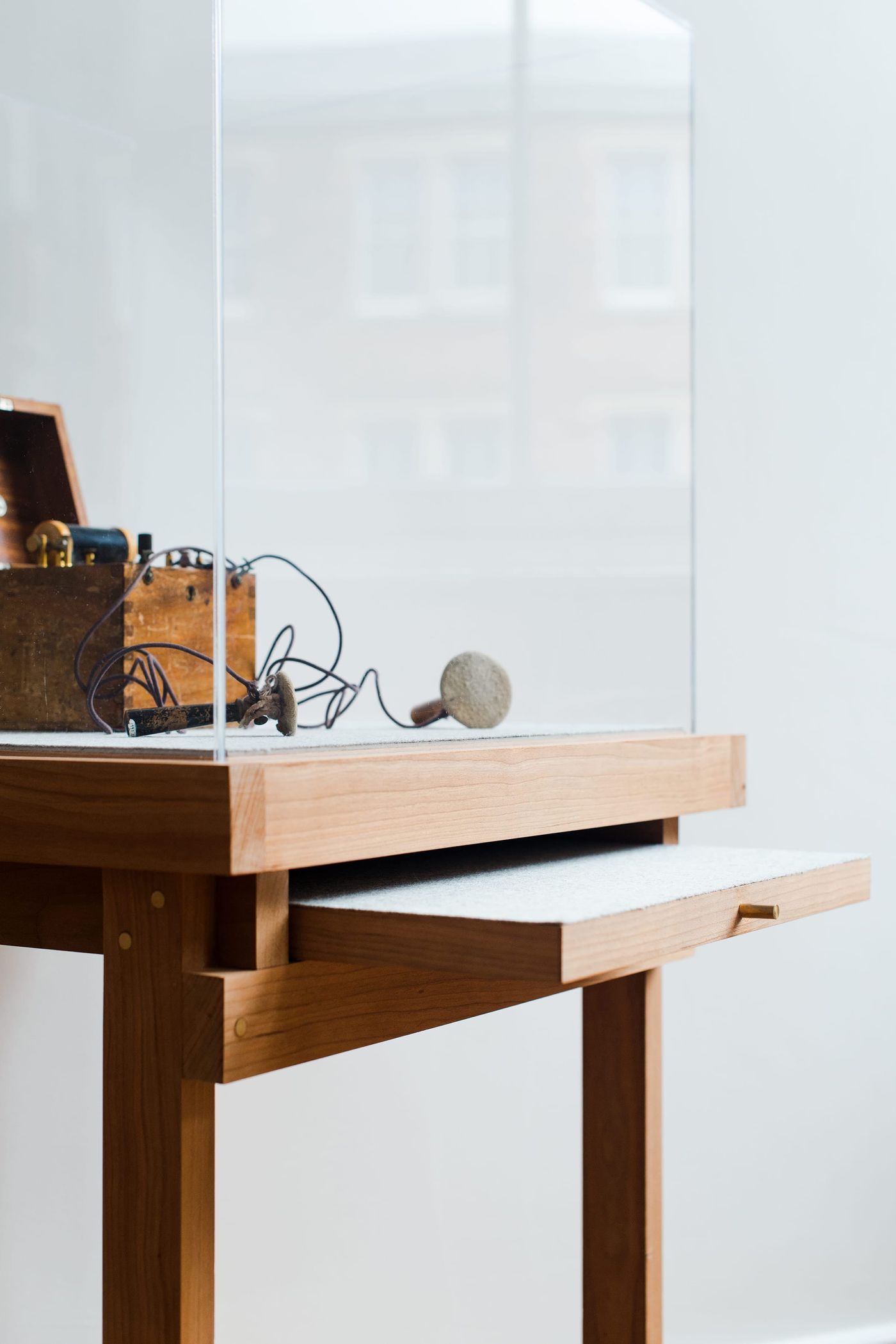 Detailed view of the bespoke solid cherry, felt and brass vitrine and furniture designed by From Works at the National Justice Museum in Nottingham.