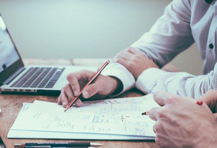 Optimierung bestehender Arbeitsabläufe auf Block mit Stift und Laptop