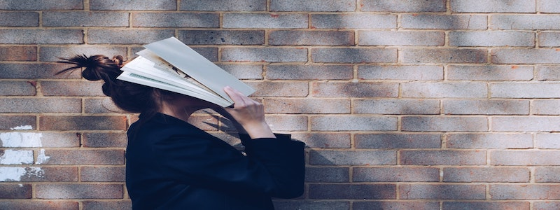 Girl hiding her face with a book