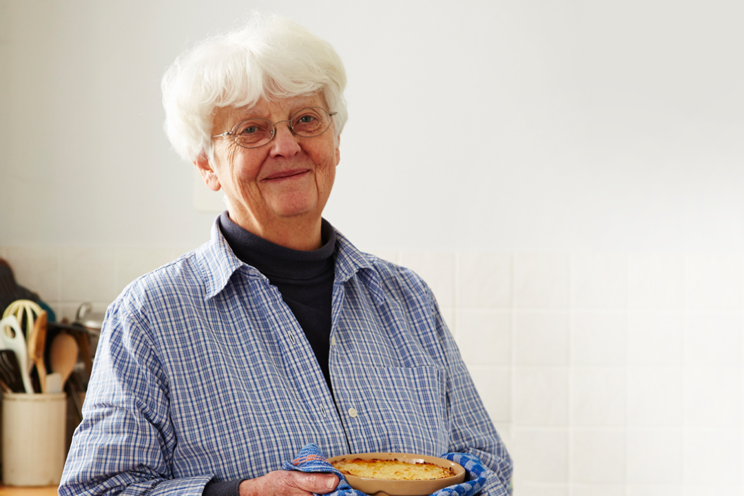 An woman holding a casserole and smiling