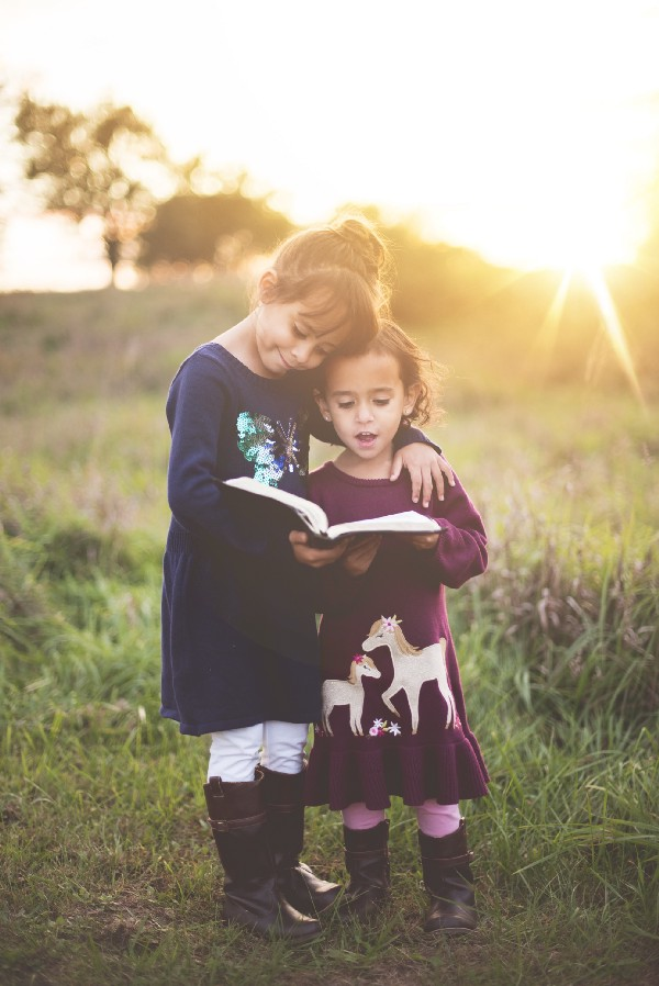 """Two young girls stand reading from a book outdoors in the sun"" by Ben White on Unsplash"