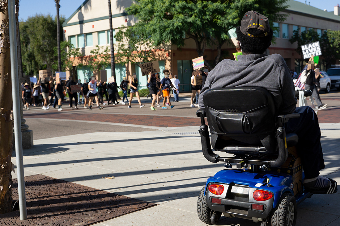 A Black USMC Veteran watches the march from his mobility scooter. Photo by Tom Mann.