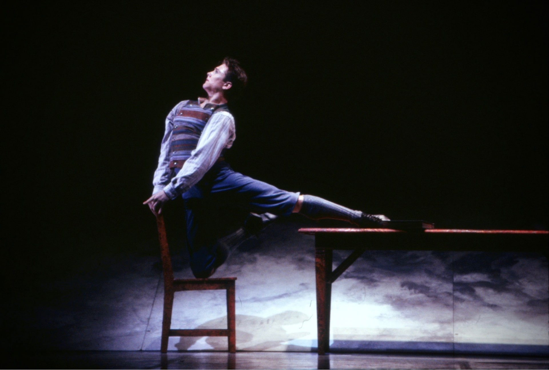 Dancer in schoolboy attire poses balanced between chair and table, in front of mottled raked stage.