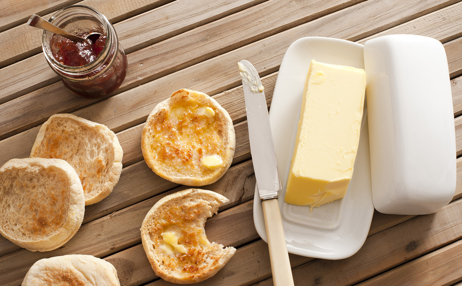 buttered english muffins on a wooden table