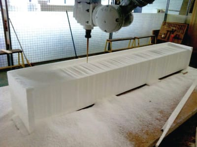 A large foam block sculpture sits on the floor, with a drill machine over it.