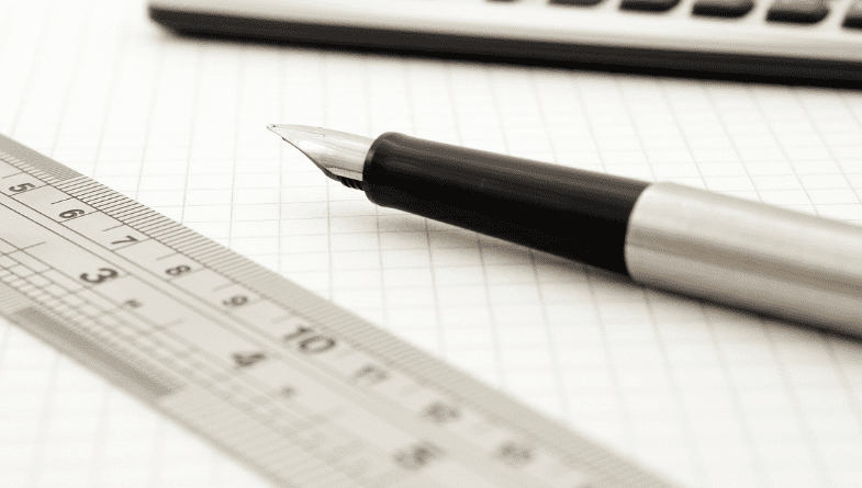 A ruler and pen lie on lined paper next to a laptop that is open to explain how to measure key performance indicators for businesses, advisers and accountants. #KPI