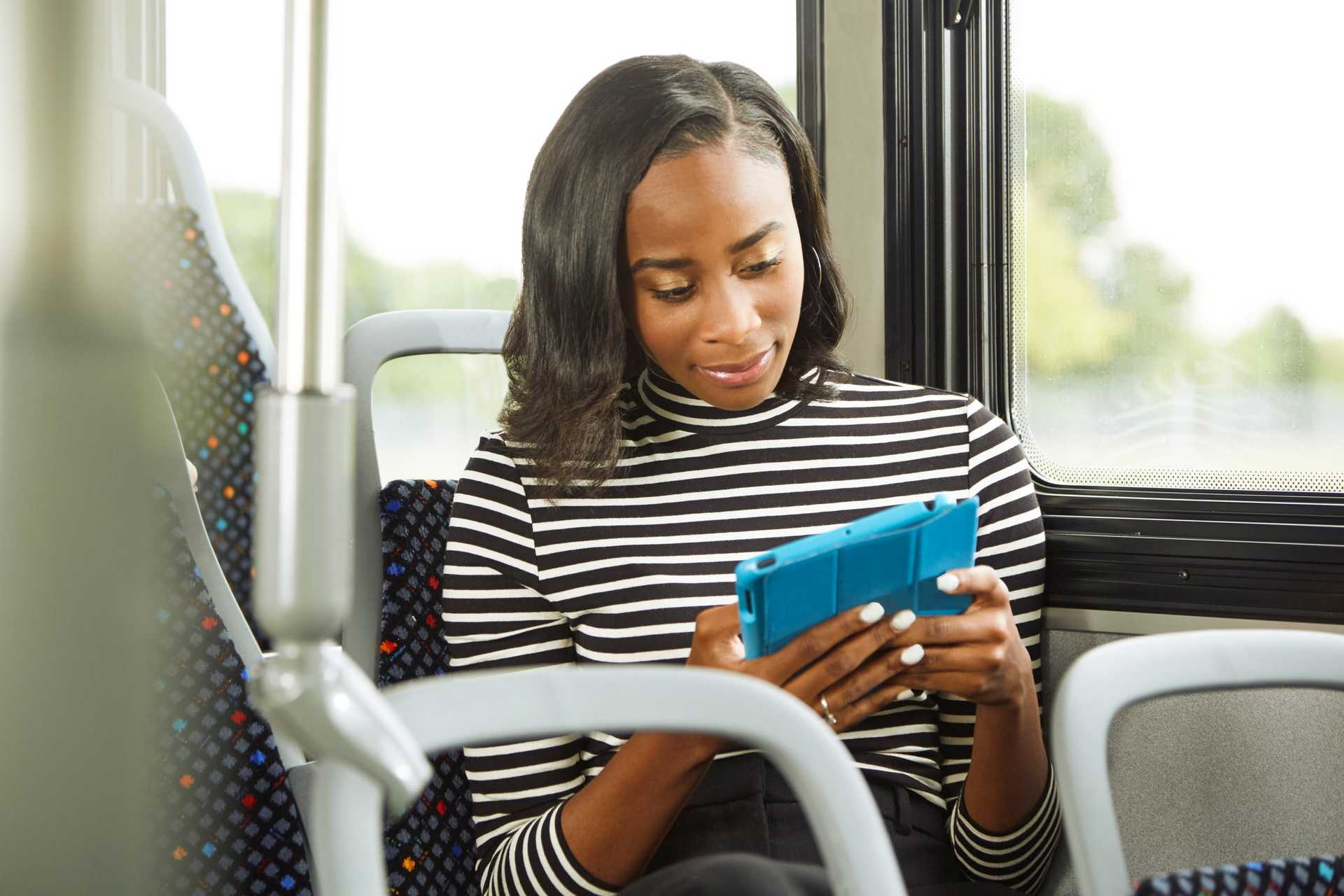 College Student on a bus using a tablet