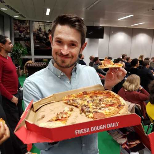 Jamie in an office, holding out a pizza