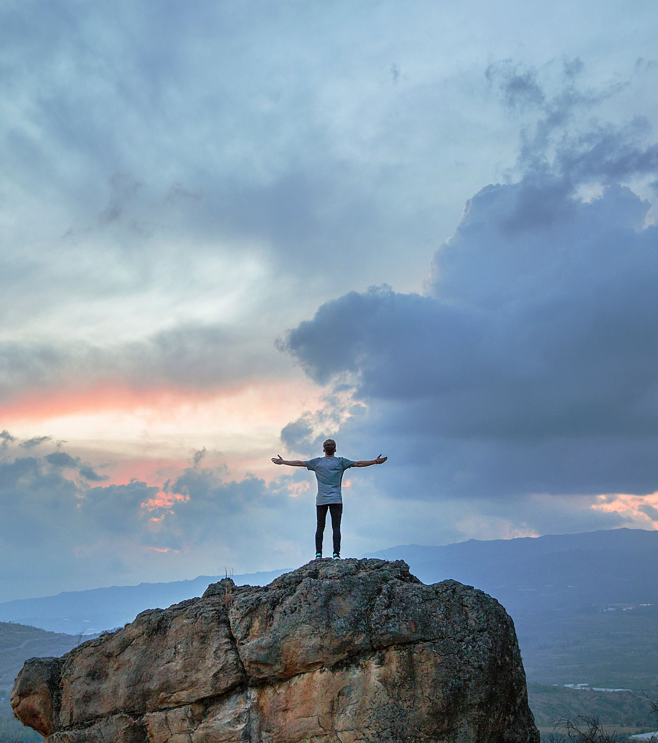 man standing on top of a large rock face with hands outstretched towards a colourful bright evening sky