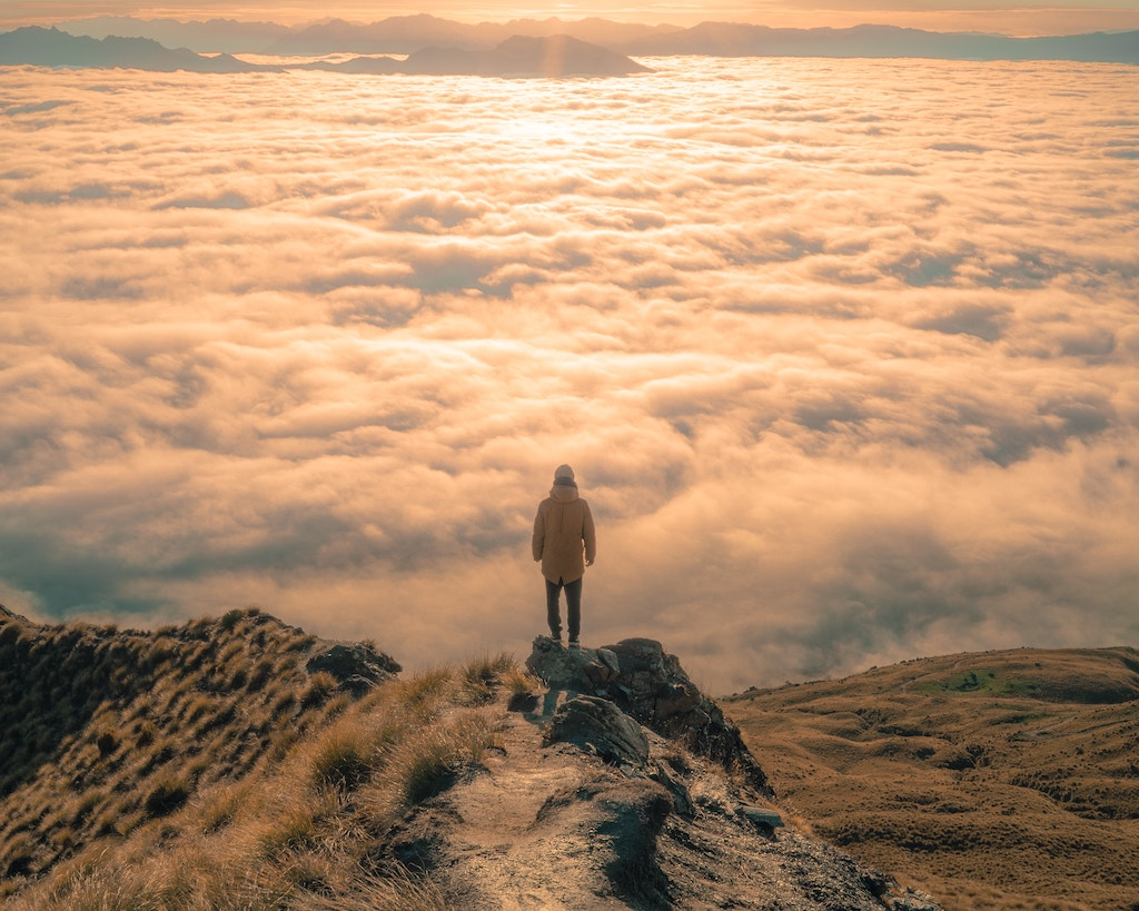 Man looking above the clouds - Photo by Alessandro Erbetta on Unsplash