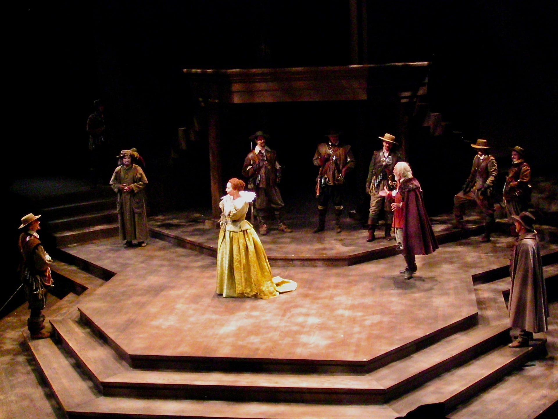 Red-haired woman in yellow gown ignores king and courtiers in dappled light.