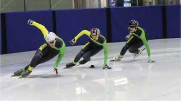 3 speed skaters turning around a corner