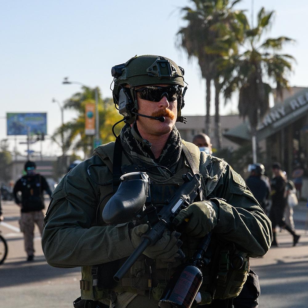 A SWAT officer stands with a pepper ball gun and a big mustache.