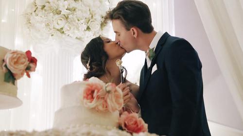 Ben and Cynthia kiss while cutting cake