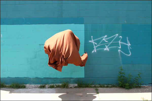 A floating rust-colored sheet of fabric seems to float, unaided, about 4 feet off the ground. The fabric is billowed and folded as though occupied inside, yet there's no evidence of a mass or volume that would occupy it.