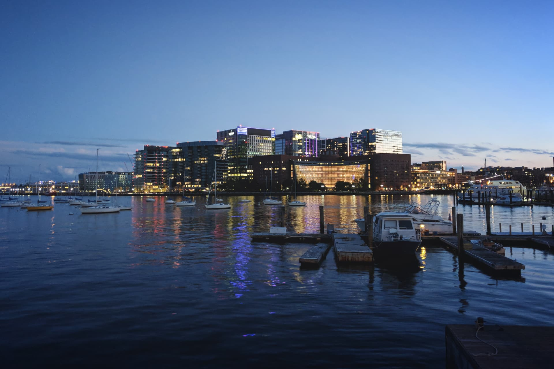 A tight cluster of buildings seen from across a small bay at dusk.