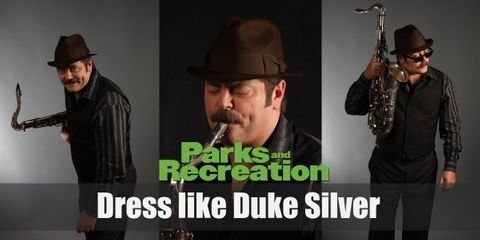 In real life, Duke Silver is actually Ron Swanson, Leslie's superior in the Parks and Recreation Department. Duke looks cool, calm, and utterly jazzy in his stage attire. He wears a red shirt underneath a grey 3-piece suit, a black fedora, and a pair of black Oxfords while he holds his precious gold saxophone.