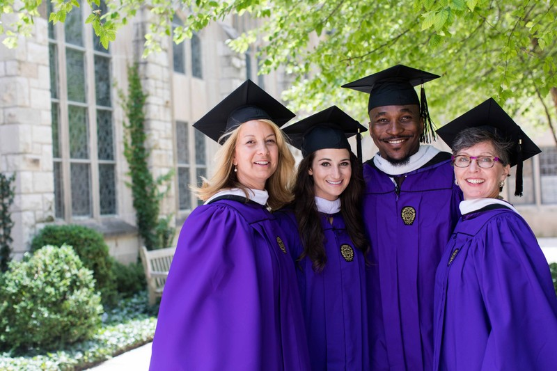 Northwestern University graduates smile for a group photo in their cap and gowns