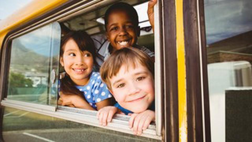 Three children on a school bus window