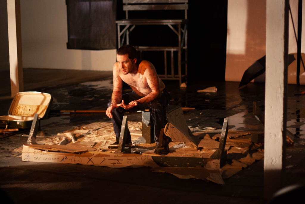Man sitting in the rubble of drywall