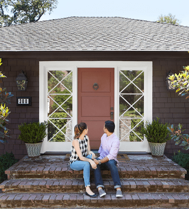 Young couple sitting on steps looking back at house.
