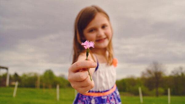 menina segurando uma flor