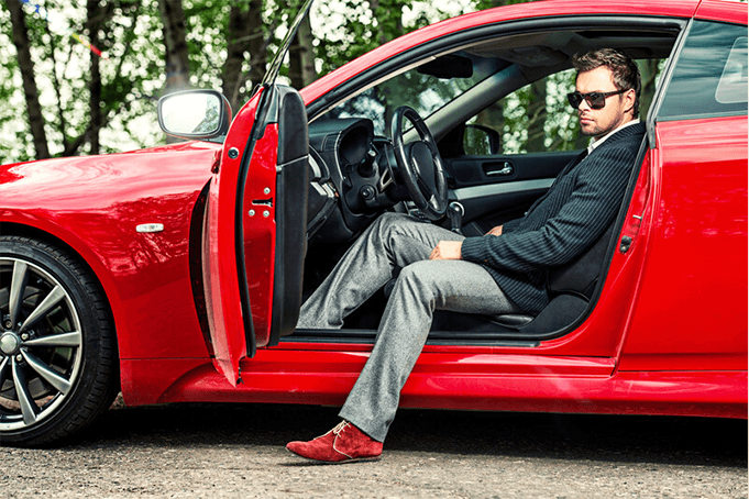 A bright red sports car with a man sitting inside