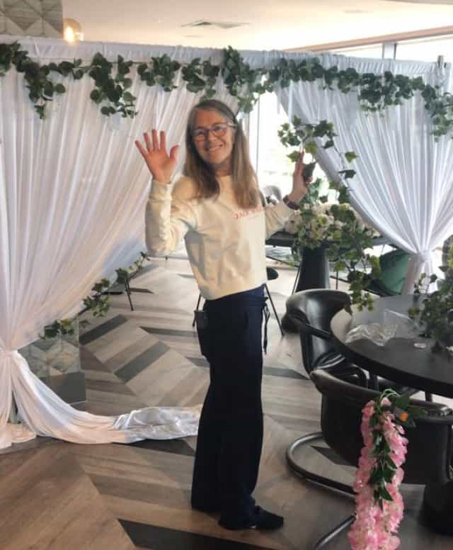 Happy lady waving with white wedding decoration around her