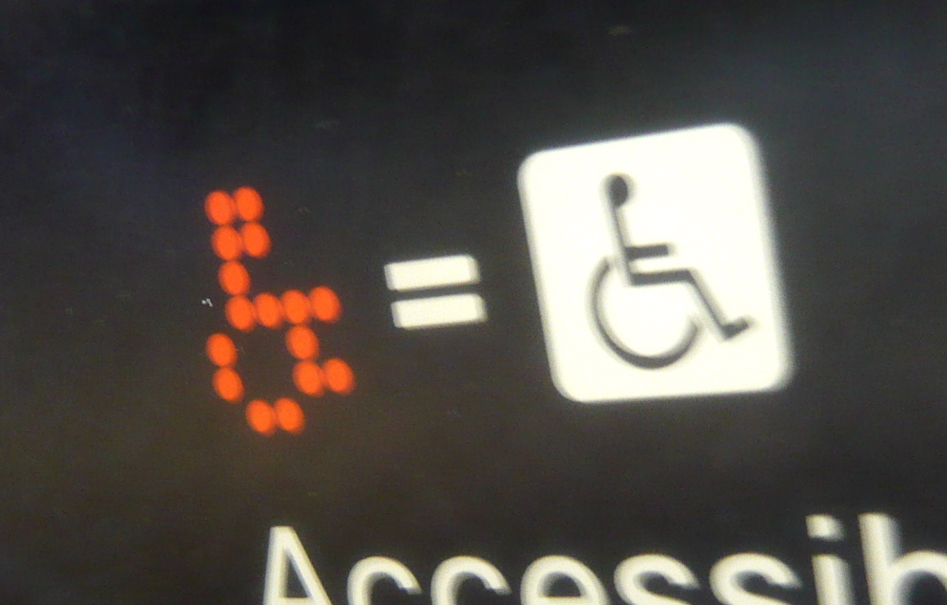 """Image: a digital dot matrix wheelchair on a screen, followed by an equal symbol, and the International Symbol of Access. Below it is a partially obscured printed """"accessible."""" Credit: Jason Eppink on Flickr."""