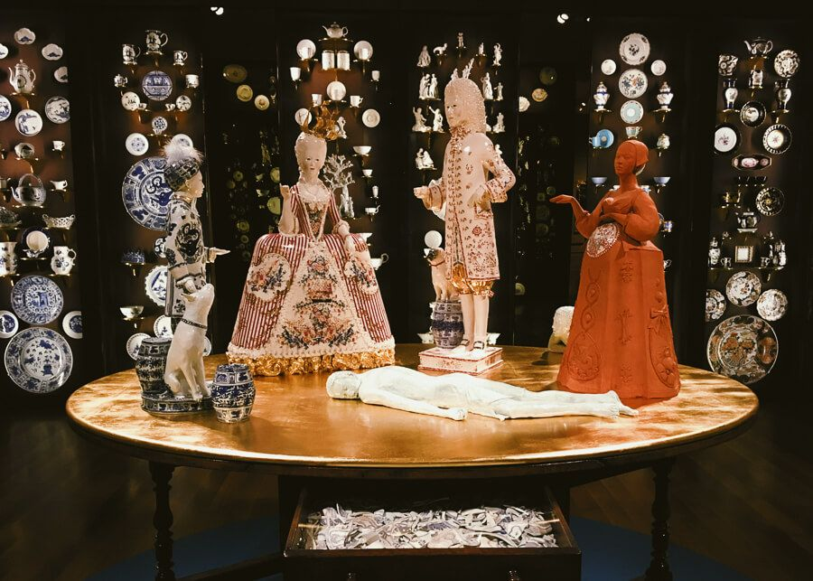 Porcelain figureines in elaborate outfits on a table. One figurine is naked and lies flat on the surface